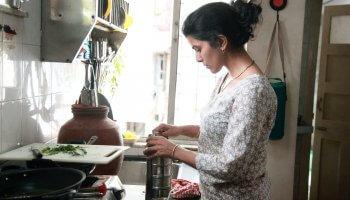 Ila (Nimrat Kaur) bereitet ihrem Mann liebevoll das Mittagessen für seine Lunchbox. Still aus Film Lunchbox