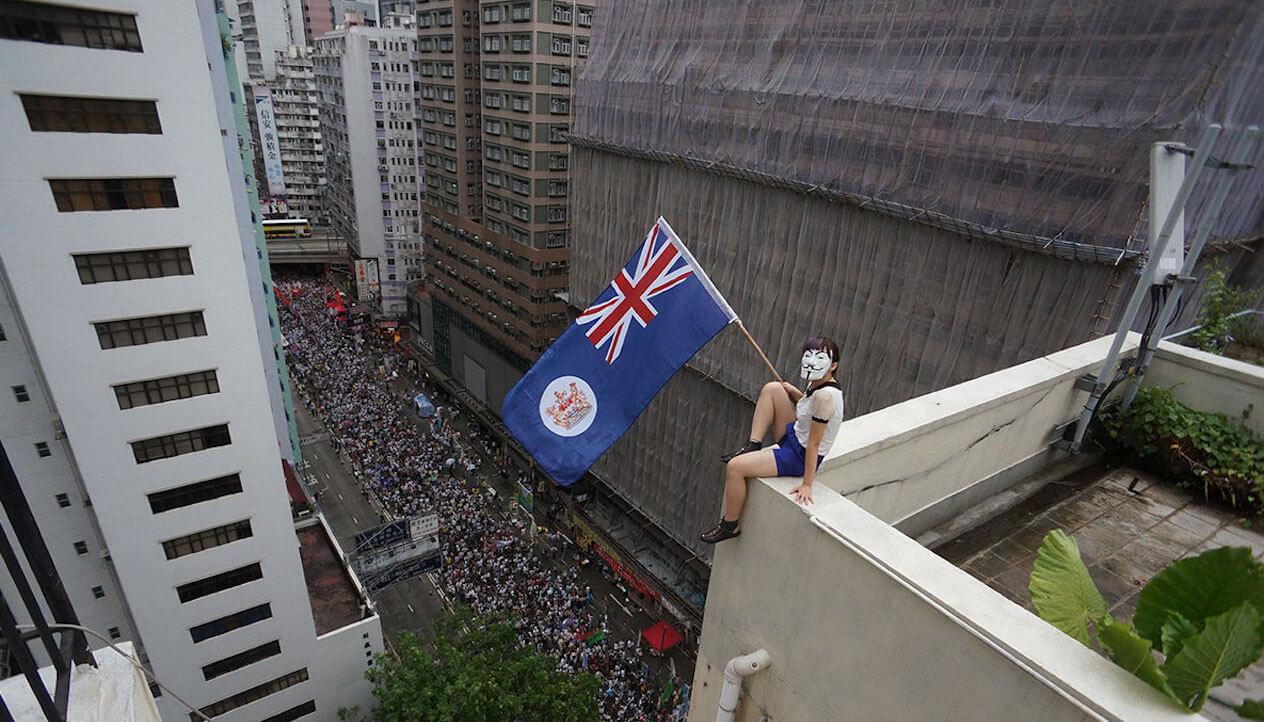 Hong Kong rooftop rebels sitzt auf dem Dach mit einer Flagge in der Hand